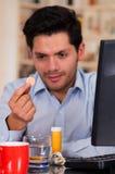 英俊的人在他的手上的拿着一种药片冒泡片剂在办公室 库存照片