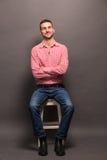 英俊的人坐一把椅子在演播室 库存图片