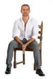 英俊的人坐椅子 免版税图库摄影