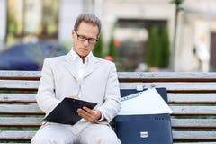 英俊的人坐长凳 免版税库存照片