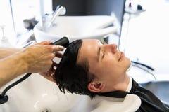 英俊的人安排他的头发洗在理发交谊厅 说谎与他的年轻人在秀丽交谊厅注视闭合 库存图片