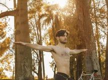 年轻英俊的人实践的体育在秋天森林里 库存图片
