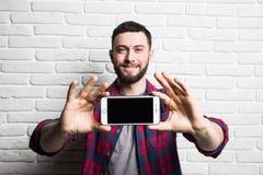 年轻英俊的人展示在一个空白的黑屏幕智能手机的食指在反对bri的背景的便装样式衣物 库存照片