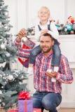 英俊的人帮助孩子装饰新年树 库存图片