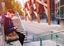 英俊的人手机室外城市街道,年轻可爱的学生偶然蓝色衬衣谈话 免版税图库摄影