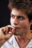 英俊的人抽烟的年轻人 图库摄影