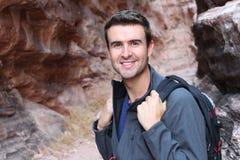 英俊的人步行在岩石峡谷的,走在自然的背包徒步旅行者 免版税库存图片