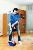 英俊的人清洁客厅 免版税库存照片