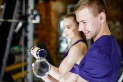 英俊的人画象在小组锻炼期间的在与附近一个的女孩的健身房 单独训练 免版税图库摄影