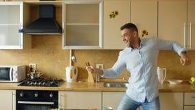 英俊的人获得乐趣在操刀与杓子和匙子的厨房,当在家时烹调早餐 免版税库存照片