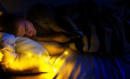 英俊的人行家,睡觉在她的白色床上,夜,梦想关于愉快的生活 免版税库存照片