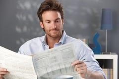 英俊的人读取报纸 图库摄影