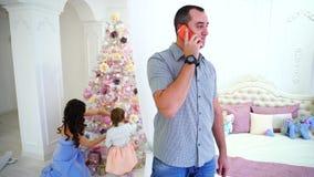 英俊的人谈话在卧室光的电话在他的妻子和女儿背景,准备庆祝 股票录像