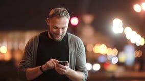 英俊的人走,微笑,使用他的智能手机并且走开 在街道的被弄脏的城市光 现代技术 影视素材