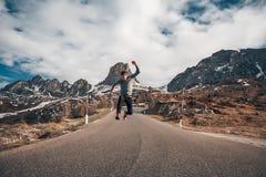 英俊的人跳跃的惊人的山背景 库存图片