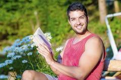 年轻英俊的人阅读书在一个绿色开花的庭院里 免版税库存照片