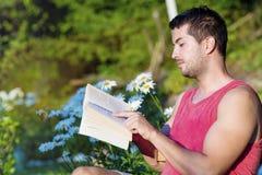 年轻英俊的人阅读书在一个绿色开花的庭院里 库存照片