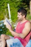 年轻英俊的人阅读书在一个绿色开花的庭院里 免版税库存图片