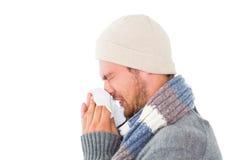 英俊的人以吹他的鼻子的冬天时尚 免版税库存图片