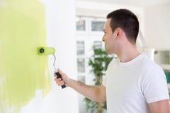 英俊的人绘画墙壁 库存图片