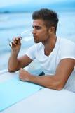英俊的人水杯酒在海餐馆在夏天 免版税库存照片