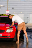 年轻英俊的人洗涤的汽车 免版税库存图片