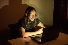 英俊的人smocking在他的计算机前面的香烟 免版税库存照片