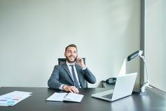 英俊的企业家讲话由电话在办公室 免版税库存图片