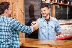 英俊的侍酒者为他的酒吧的顾客服务 免版税库存照片