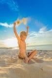 英俊的八年海滩的男孩执行杂技的剪影 图库摄影