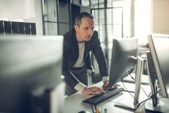 英俊的兴旺的商务伙伴的商人键入的电子邮件 免版税库存照片