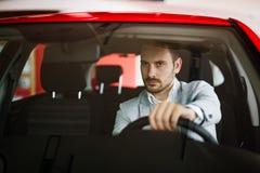 英俊的典雅的严肃的人驾驶一辆现代汽车 免版税图库摄影