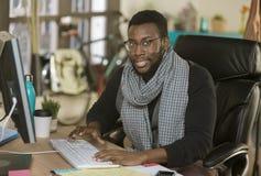 英俊的创造性的商人在键盘的一个办公室 库存照片