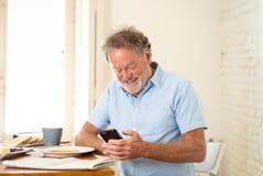 英俊的前辈退休了使用充满喜悦的老人手机,当食用早餐在家时 库存照片