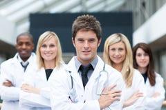 英俊的医生他主导的小组年轻人 免版税库存图片