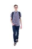 英俊的十几岁的男孩正面图有背包走的孤立的 免版税库存照片