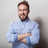 年轻英俊的友好的人画象蓝色衬衣的 在浅灰色的背景的演播室照片 免版税库存图片