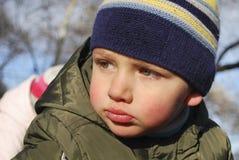 英俊的哀伤的男孩在秋天森林里。 免版税库存照片