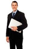 英俊的商业主管藏品膝上型计算机 库存图片
