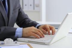 英俊的商人与膝上型计算机一起使用在办公室 图库摄影