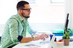 英俊的商人与膝上型计算机一起使用在办公室 库存照片