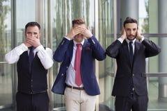 英俊的商人作为三只明智的猴子 免版税库存图片