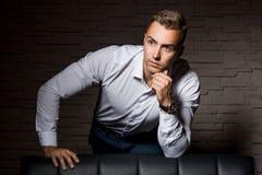 年轻英俊的商人依靠在确信的姿势的皮革长沙发 免版税库存照片