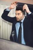 年轻英俊的商人做头发 免版税库存照片