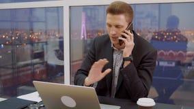 英俊的商人叫由在工作场所的手机在营业所 股票录像