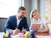 英俊的商人和办公室妇女与在被弄脏的背景的片剂一起使用 办公室会议概念 免版税库存照片