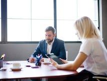 英俊的商人和妇女与在被弄脏的背景的片剂一起使用 办公室会议概念 复制空间 免版税库存图片