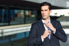 年轻英俊的商人在都市背景中的调整一条领带 免版税库存照片