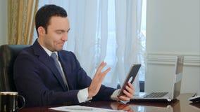 英俊的商人开关于片剂的会议有在书桌上的文件的在办公室 免版税库存图片
