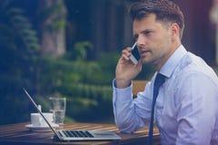 英俊的商人谈话在手机,当使用膝上型计算机时 免版税库存图片